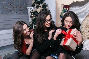 Beautiful girl opening Christmas gifts
