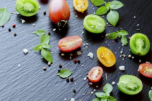 Red and black halves of tomatoes with green leaves basil
