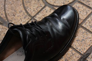 Hands polish leather black shoes