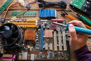 man soldering computer hardware