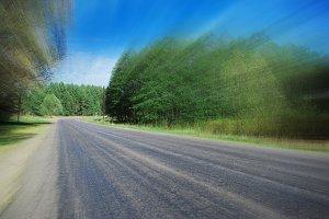 asphalt road between green trees