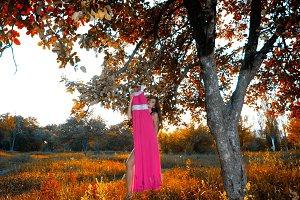 woman hiding behind a pink dress,
