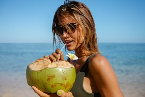 Attractive woman drinking coconut