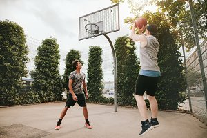 Two friends playing basketball