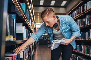 Student looking for a book in shelf