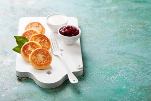 Cottage cheese pancakes Russian syrniki with cranberry jam and yogurt