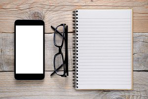 Smartphone, glasses and notepad
