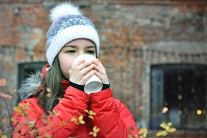 Girl drinks coffee in the winter