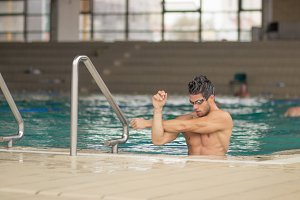 swimmer stretching inside water pool