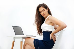 Young Caucasian woman having chronic back pain / backache / office syndrome while working with laptop on white desk over white isolated background