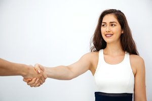 Beautiful business woman in smart casual dress shaking hands with male colleague - business partnership concept and business negotiation