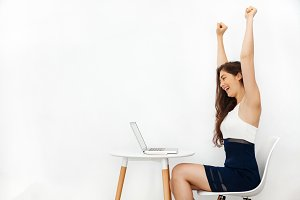 Young beautiful Caucasian woman having arms raised up as she has won over something in white isolated background with copy space