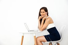 Beautiful Caucasian smiling woman talking on the phone while using laptop on white desk over white isolated background