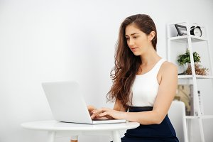 Beautiful Caucasian woman working on laptop on white desk over white isolated background with copy space