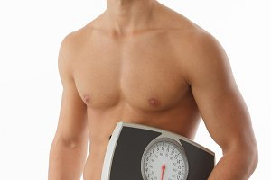 Fit man holding scale