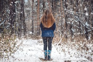 Outdoor portrait of beautiful young girl with long hair standing backwards in a winter forest while snowing. Woman in snowy woods nature landscape