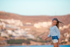 Adorable happy smiling little girl on beach vacation in Greece