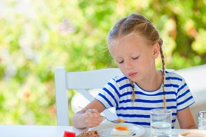 Adorable little girl having breakfast at outdoor cafe early in the morning
