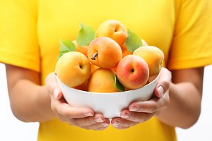 Woman hands keeping crockery with mellow apricots.