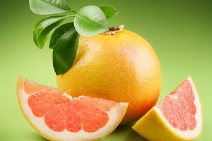 Ripe grapefruit with segment on a green background