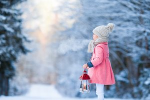 Adorable little girl wearing warm coat outdoors on Christmas day holding flashlight