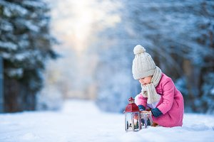 Adorable little girl with latern in frozen forest on Christmas at winter day