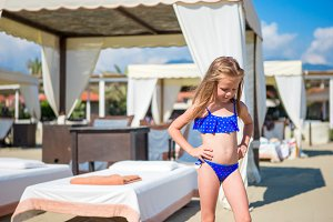 Adorable happy smiling little girl on beach vacation near sunbeds
