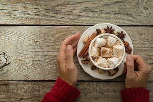 Hands holding hot chocolate with marshmallow and cinnamon