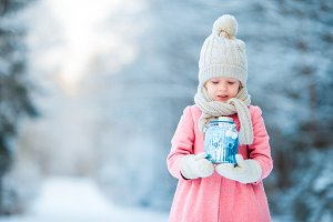 Adorable little girl with flashlight in frozen forest on Christmas at winter day