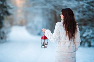 Girl holding Christmas lantern outdoors on beautiful winter snow day