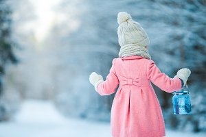 Little girl holding Christmas lantern outdoors on beautiful winter snow day