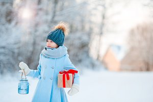 Little girl holding Christmas lantern and present on New Year outdoors on beautiful winter snow day