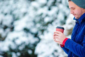 Young caucasian man drinking hot coffee in frozen winter day outdoors