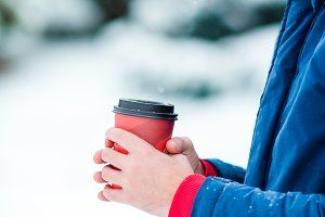 Closeup coffee to go in male hands at frozen winter day outdoors