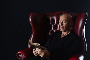 Bald man reading a book/bible