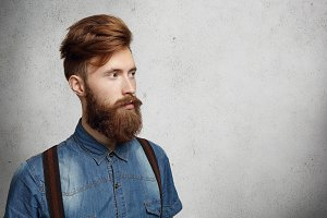 Casual young man with stylish fuzzy beard dressed in denim shirt and suspenders looking ahead of him at blank wall with copy space for your text or promotional content. Isolated shot, horizontal