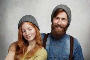 Cheerful bearded hipster in denim shirt laughing while hugging his beautiful redhead girlfriend who is looking at him with sly mysterious smile. Two best friends in knitted hats relaxing together