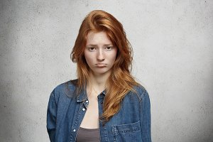 Human face expressions and emotions. Portrait of pretty teenage girl with long red hair and freckles wearing denim jacket looking with upset and unhappy face, pouting and feeling disappointed