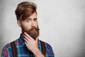 Headshot of young fashionable Caucasian man with stylish haircut, touching his perfect thick fuzzy beard while thinking of something important, standing against blank concrete wall background