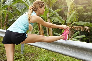Caucasian sportswoman with braid stretching and warming up her legs, preparing her muscles before going on long run. Tired female jogger in sportswear taking break leaning on country road guardrail