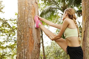 Healthy lifestyle concept. Young blonde woman runner with beautiful athletic body stretching in tropical forest, placing her right leg on tree, warming up before serious physical workout outdoors