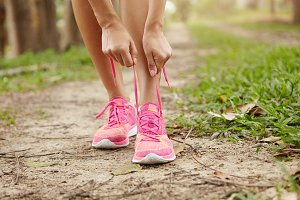 Cropped shot of young woman runner tightening running shoe laces, getting ready for jogging exercise outdoors. Female jogger lacing her pink sneakers standing on forest path before morning run