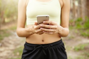 Cropped image of woman training outdoors and tracking her fitness route on cell phone. Female athlete holding electronic device, using fitness app to monitor her progress during running exercise