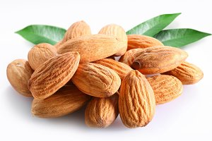 Almonds with leaves on white background