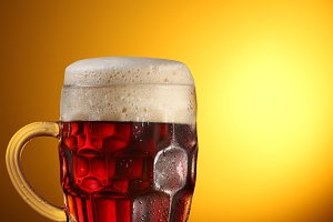 glass of dark beer on a brown background