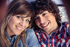 Couple in love taking selfie lying over bed