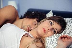 Thoughtful woman lying near her sleeping boyfriend