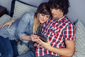Happy couple in love looking electronic tablet on bed