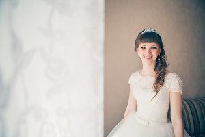portrait of a young bride standing against  wall