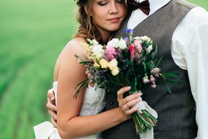 portrait of the bride and groom with a bouquet on the green field